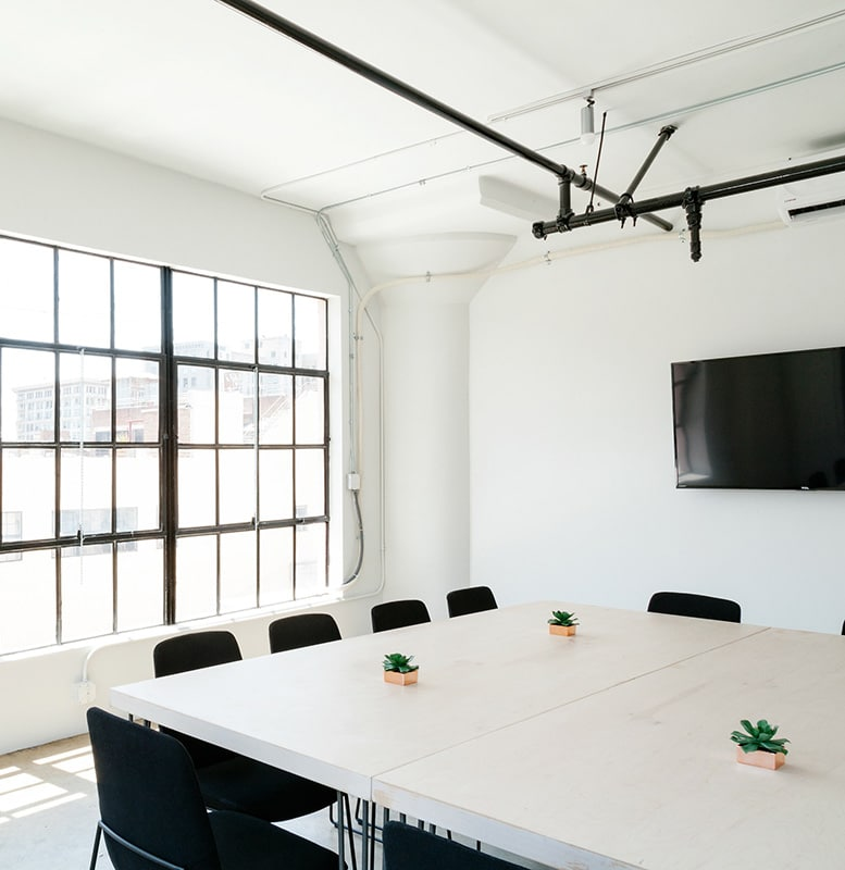Clean white conference room with black chairs and a tv.