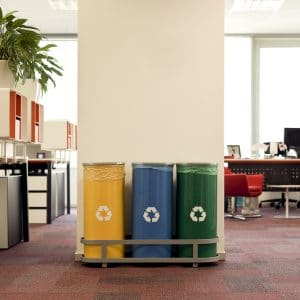 Yellow, blue, and green recycle bins set up in an office