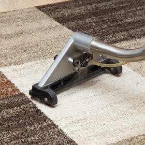 Silver carpet cleaning machine spraying cleaner on office floor