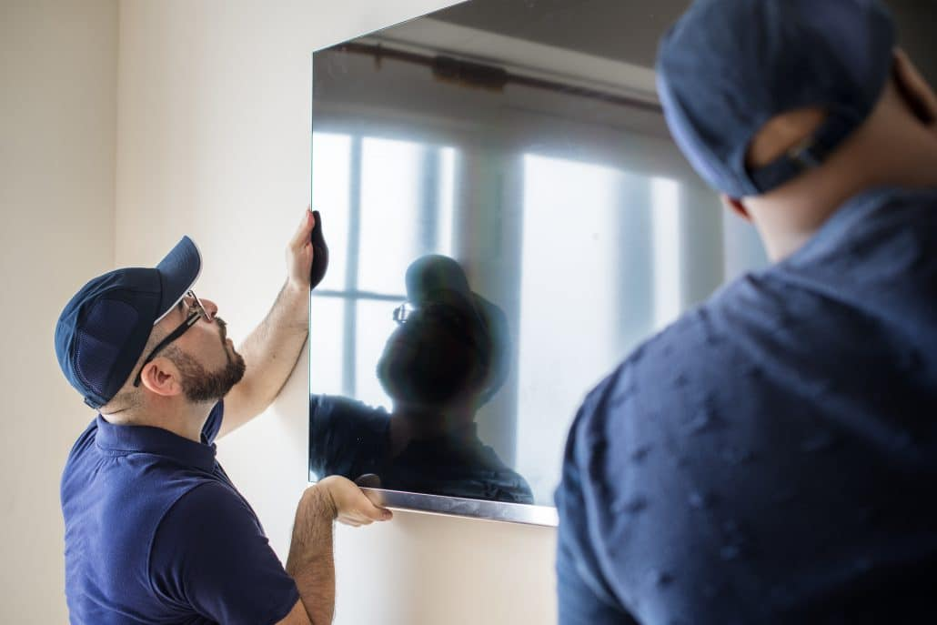 Two men installing a tv to a wall.