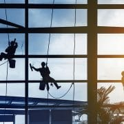 3 window cleaners hanging from harnesses cleaning windows.