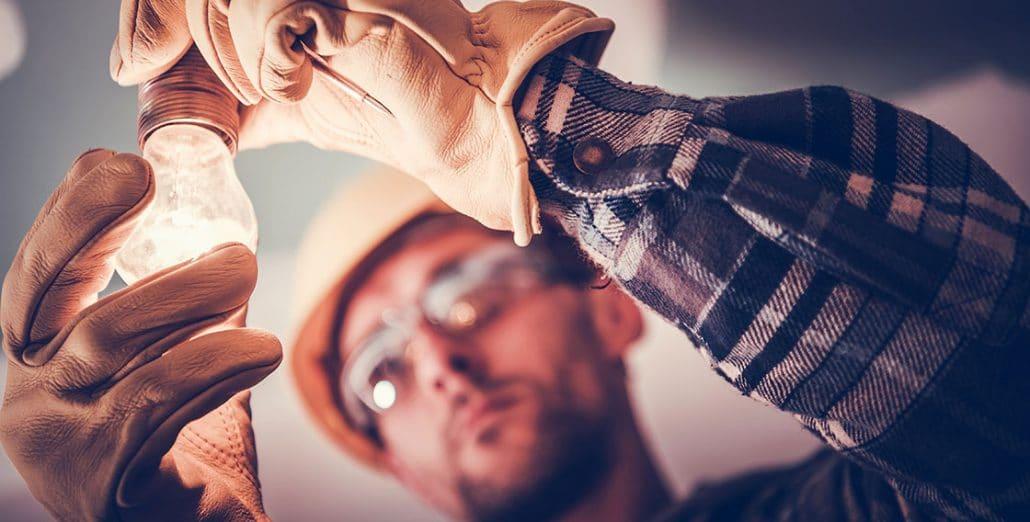 Electrician fixing light bulb