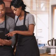 Two people in aprons looking at a tablet.