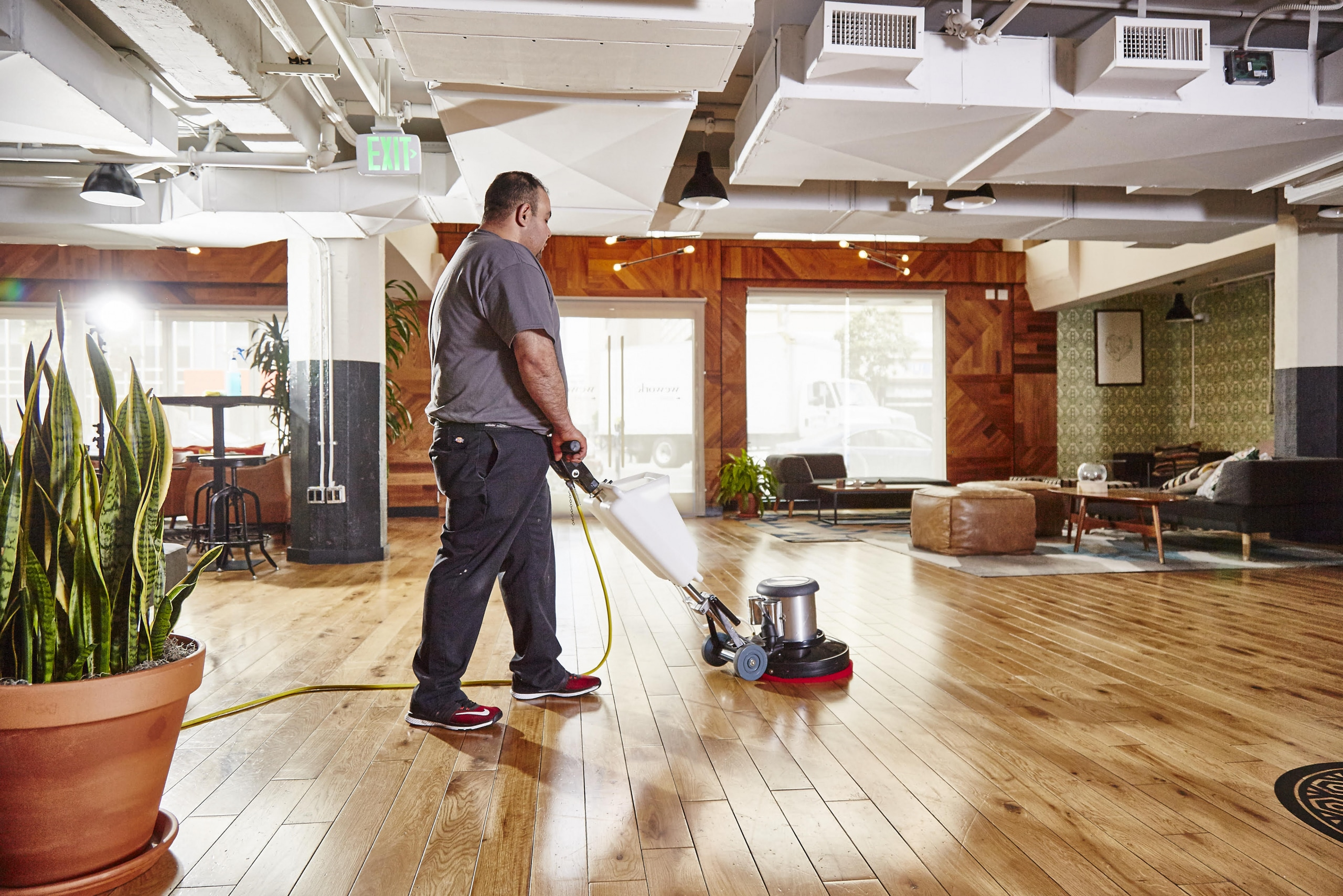 Man cleaning a hardwood floor with a machine.