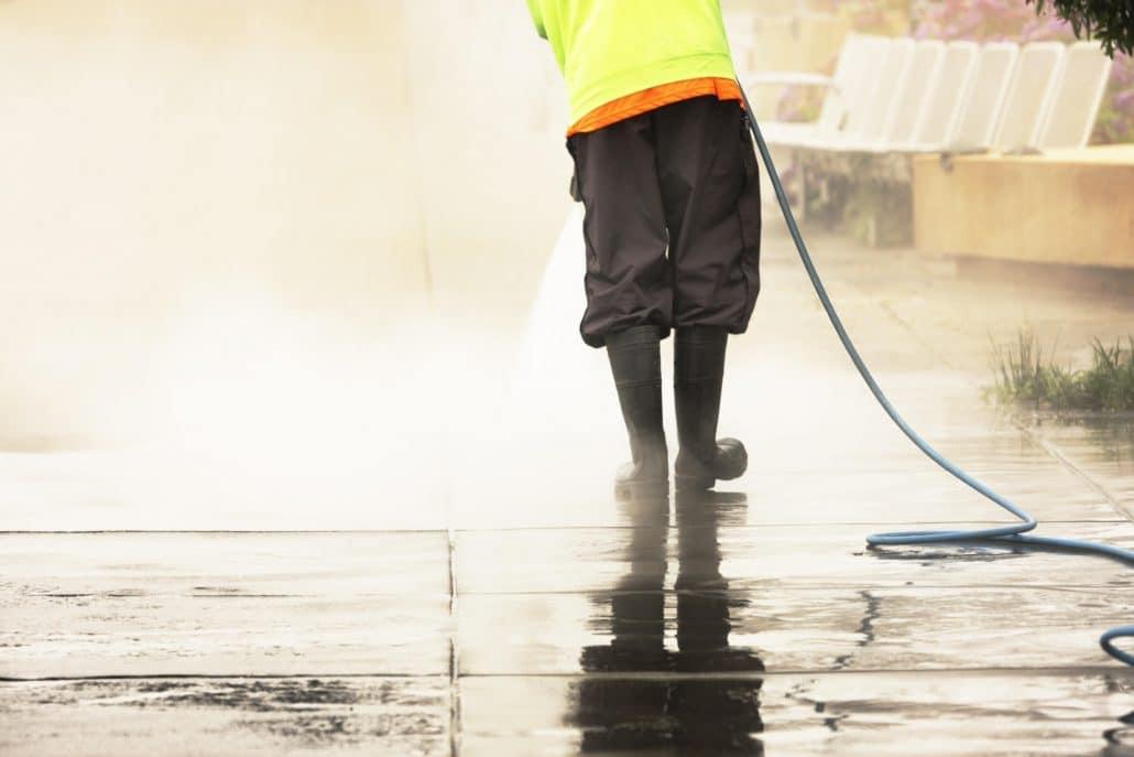 City worker using pressure washer on sidewalk.