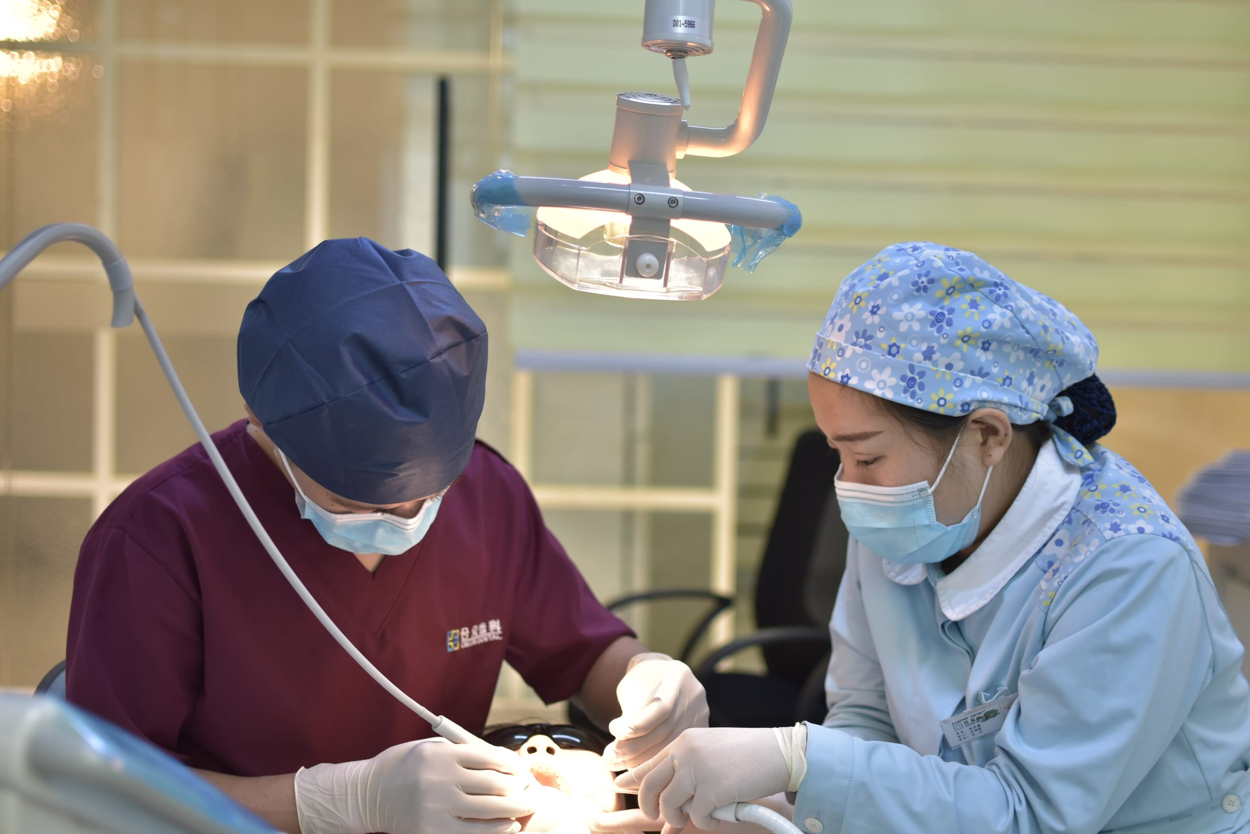 Two dentists cleaning a patient's teeth.