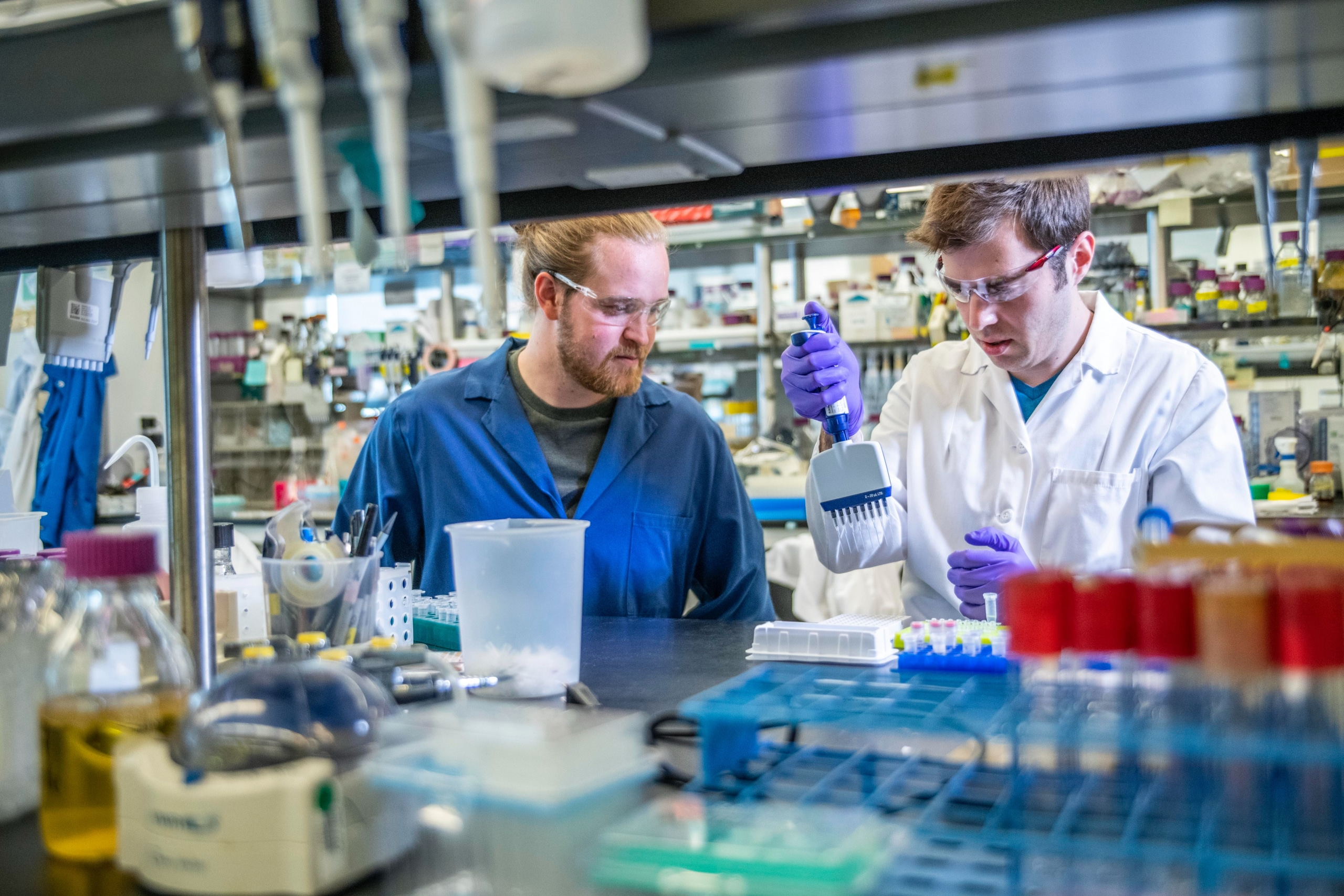 Two men wearing lab coats in a lab.