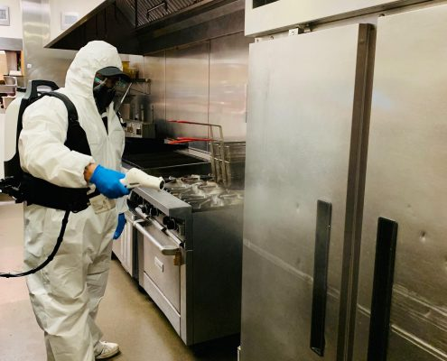 Man in protective suit cleaning and disinfecting a kitchen.