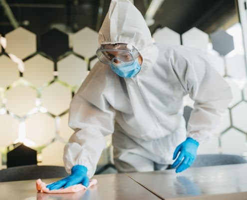Man in protective suit cleaning and disinfecting table.