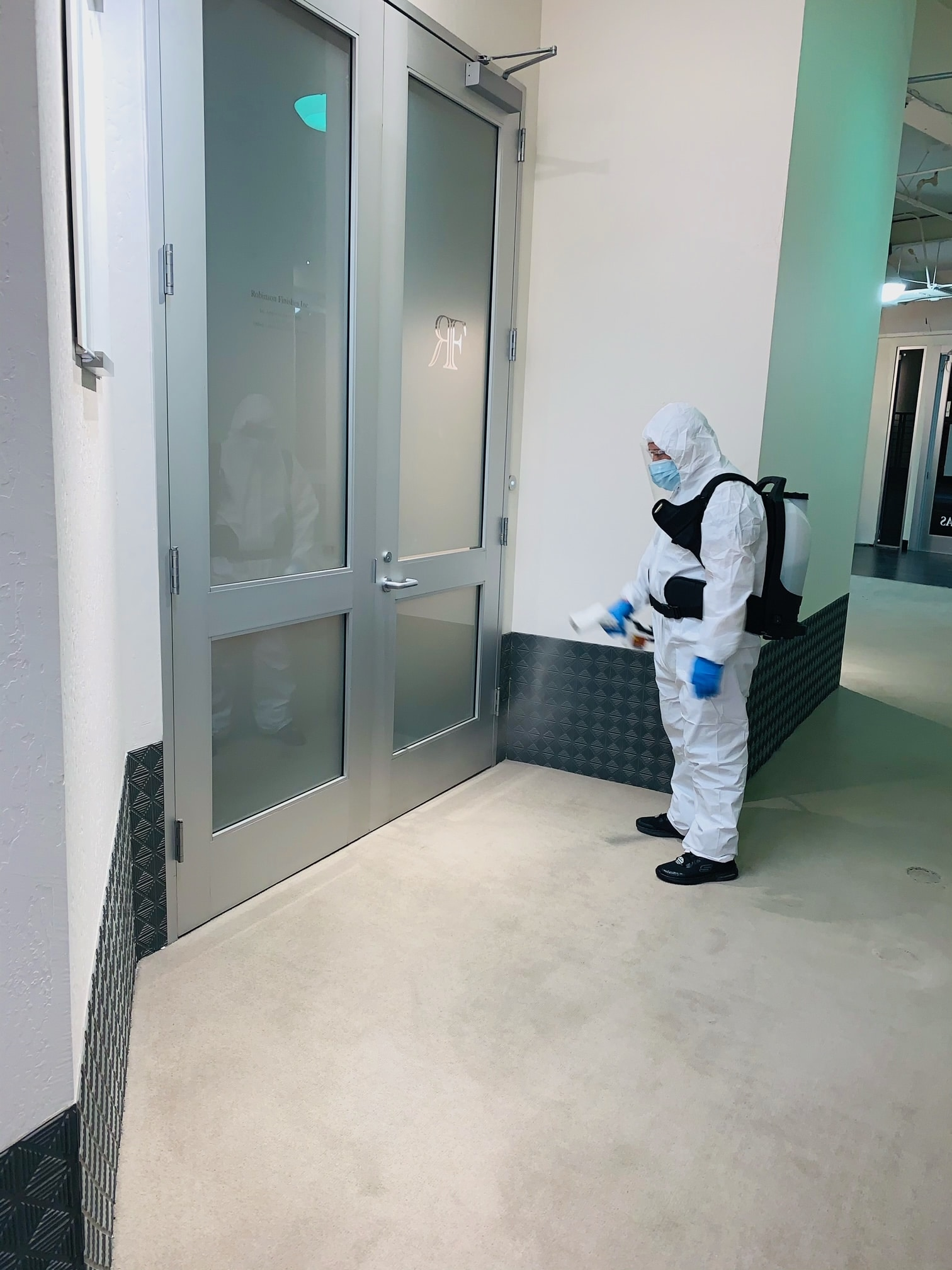 A professional disinfecting a doorway