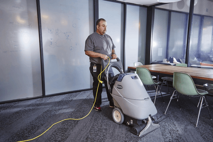 A janitor cleaning the carpet at a commercial site