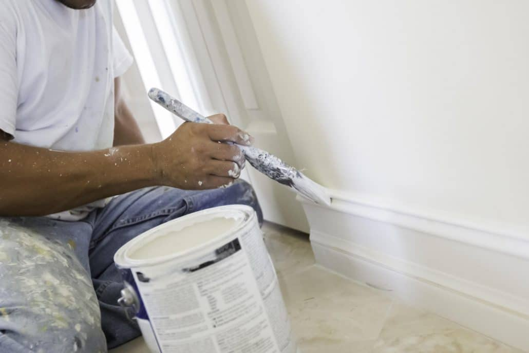 A man painting the walls white